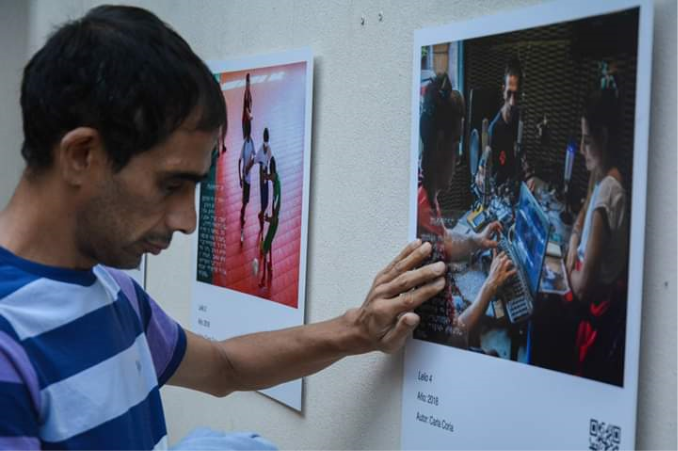 """Lelio Sánchez, one of the persons portrayed in the accessible photographic exhibition """"We Feel, runs his hand over the inscription in Braille displayed over his photograph at the opening of the Exhibition in MediHome, in the City of La Plata ."""