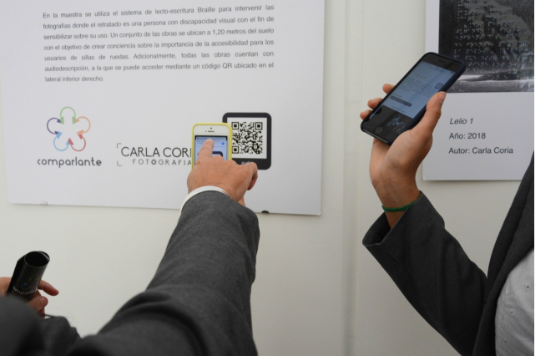 """On a wall, the curatorial text of the accessible photographic exhibition """"We Feel"""" is displayed, which includes a QR code that is being scanned by two persons with their smartphones."""