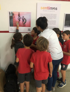 """A group of children, students of the Primary School of the Estudiantes de La Plata Club, surround Carla Coria, photographer in charge of the accessible photographic exhibition """"We Feel"""", while observing a photography and one of the children points to the Braille description displayed over its surface."""