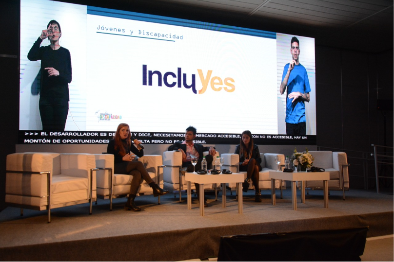 Lorena Julio, Co-Founder and President of Fundación Comparlante presenting IncluYes at the Global Disability Summit, Buenos Aires 2019. In the background there is a screen with the IncluYes logo, and two Sign Language interpreters on the sides. On stage Lorena appears seated with two other panelists addressing the audience.