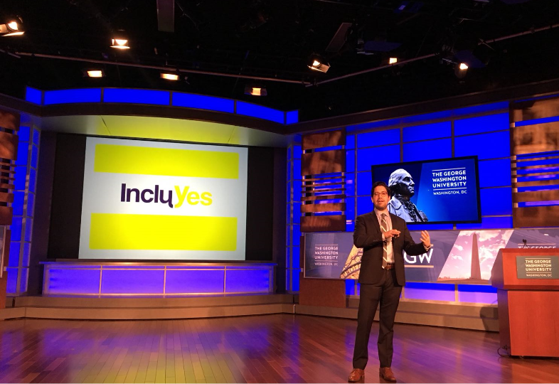 José Clautier, Institutional Relations Officer of Fundación Comparlante presenting IncluYes at the Global Public Policy Summit at George Washington University. In the background there is a screen with the IncluYes logo, and another with the University's logo. José appears on stage addressing the audience.