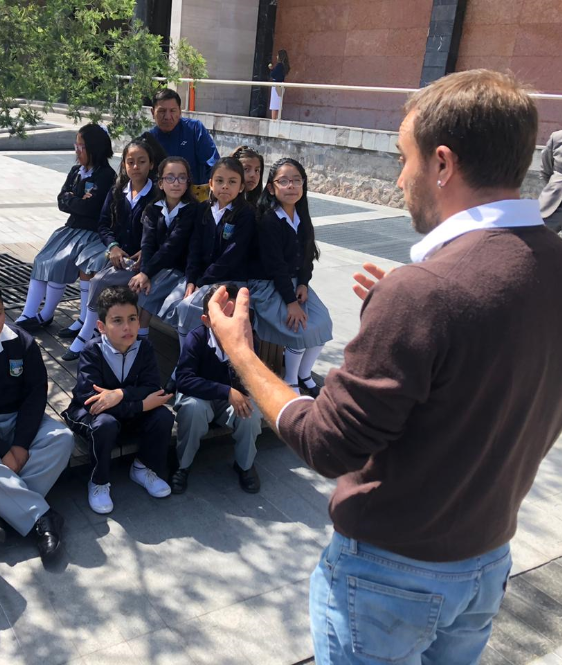 Andrés Julio, artist in charge of the Accessible Art exhibition speaking to a group of students on the grounds of the National Assembly of Ecuador. 6- In the grounds of the National Assembly, a group of Parliamentarians are standing, to one side a Sign Language interpreter appears interpreting the event.