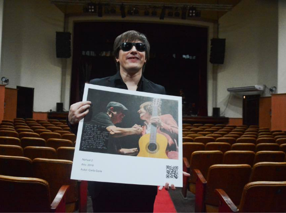 """The singer Nahuel Pennisi poses in an empty theater holding in his hands the photograph in which he is portrayed together with Silvio Rodriguez, which is part of the accessible photographic exhibition """"We Feel""""."""