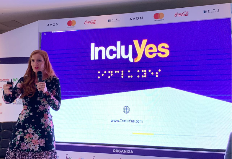Lorena Julio, Co-Founder and President of Fundación Comparlante presenting IncluYes at the Woman Economic Forum, Cartagena 2019. In the background there is a screen with the IncluYes logo, in the center of the stage Lorena addressing the public.