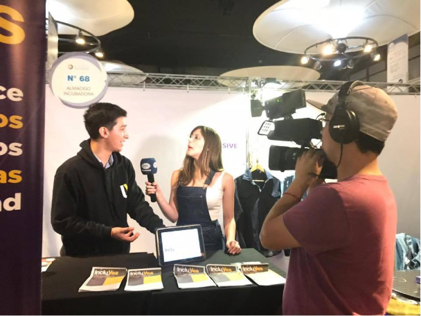 Pablo Ojeda, is interviewed by a television channel from an incluYes showroom presentation stand at an entrepreneurship fair in Chile.