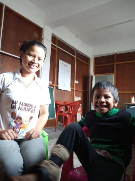 """A teacher and a boy from India smiling. She is wearing a shirt with the logo and characters from """"My World My Way First Edition""""."""
