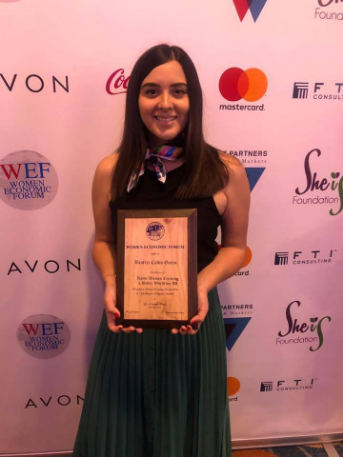 """Beatriz Calvo Garro, illustrator of the stories of the International Literary Contest """"My World My Way"""" holds in her hands the award received at the Women Economic Forum 2019 in Cartagena, Colombia."""
