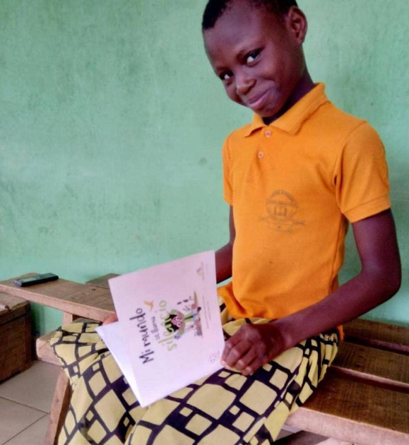 """A Kenyan boy smiles while holding in his hands the book """"My world was called silence"""", winning story of the Second Prize at the International Literary Contest """"My World My Way""""."""