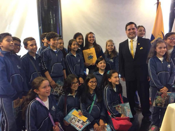 """Sebastian Flores, Co-Founder and Executive Director of Fundación Comparlante poses with Agustina Irene Abdo, Winner of the First Prize at the International Literary Contest """"My World My Way"""" and her classmates in the National Assembly of Ecuador."""