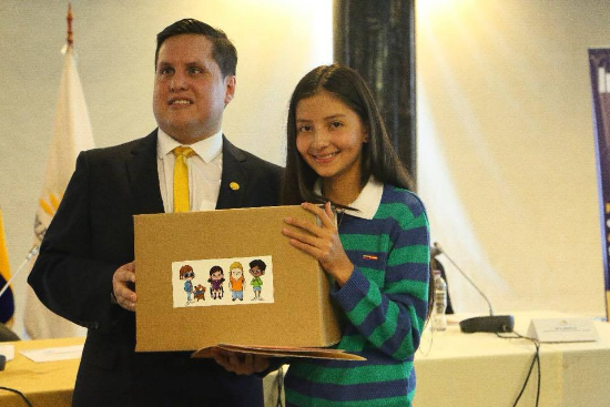 """Sebastian Flores, Co-Founder and Executive Director of Fundación Comparlante poses with Agustina Irene Abdo, Winner of the First Prize at the International Literary Contest """"My World My Way"""". The girl is receiving the award at the National Assembly of Ecuador."""