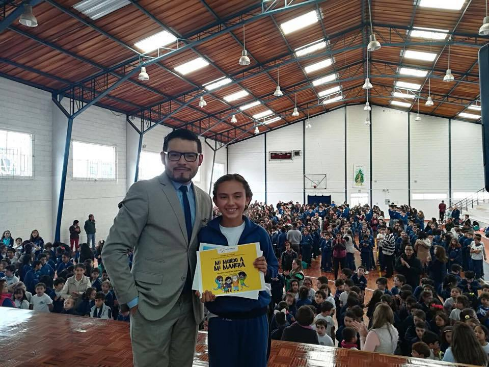 """Roberto Jaramillo, Project Manager of Fundación Comparlante, presents the Second Prize at the International Literary Contest """"My World My Way"""" to Ariana Valentina Valenzuela. In the background there is a multipurpose school room with a large number of children posing for the photo. Ariana holds with her hands the diploma as wiener."""