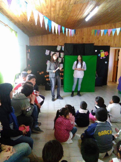 """Ana Maidana, Secretary of Fundación Comparlante, participating in the """"Reading Marathon"""" in Juan A. Pradere. Ana is standing reading a story while surrounded by a group of children who listen to her sitting on the floor."""