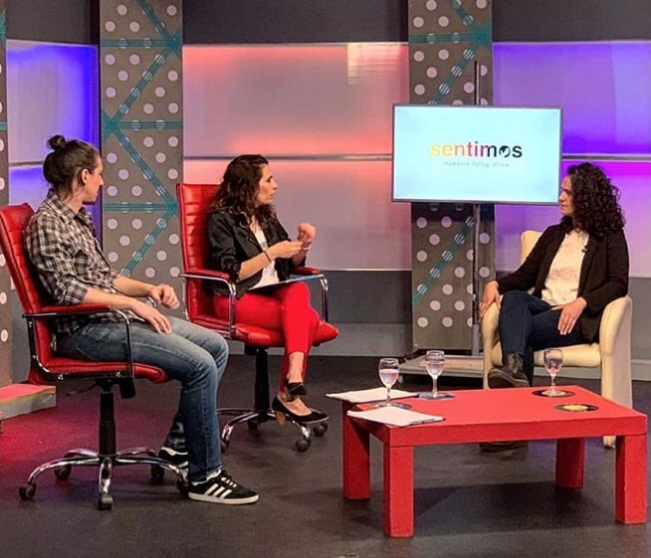 """In a television studio, Carla Coria, photographer in charge of the accessible photographic exhibition """"We Feel"""" appears next to two interviewers. They are all sitting in red chairs. In the background there is a screen with the logo of the exhibition on a white background."""