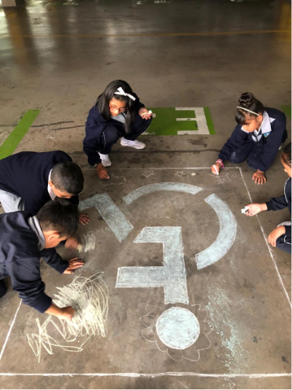 A group of children performing an artistic intervention on the floor of the Parking Lot of the National Assembly of Ecuador, an action framed in the Accessible Art exhibition, carried out in December 2019 in Quito, Ecuador.