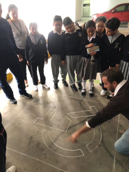 """Andrés Julio, artist in charge of the Accessible Art exhibition, kneeling while giving instructions to a group of children on how to color some silhouettes of the """"disability"""" symbol on the floor of the parking lot of the National Assembly of Ecuador."""